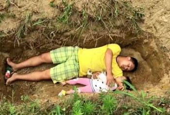 پدری که با دختر دو ساله اش در یک قبر بازی می کند!+عکس